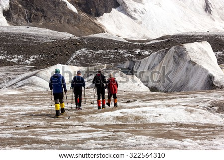 Mountaineers Walking Across Large Glacier Group of Mountain Climbers with High Altitude Boots and Clothing Crossing Ice Section During Ascent of Alpine Expedition in Asia Mountain Area - stock photo