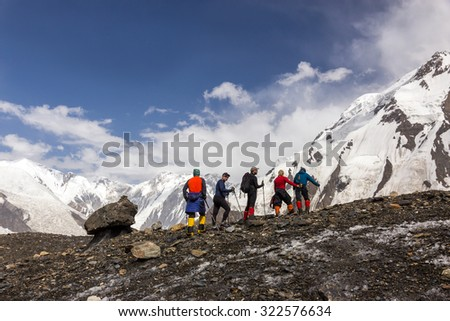 Mountaineers Walking Across Large Glacier Group of Mountain Climbers with High Altitude Boots and Clothing Crossing Glacier Surface with Unusual Rock Mushroom on Foreground and Blue Sky background - stock photo