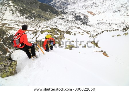 Mountaineers walking with care on snow covered mountain in adverse weather - stock photo