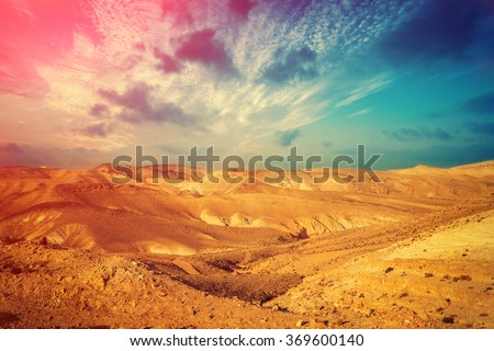 Mountainous desert with colorful cloudy sky. Judean desert in Israel at sunset - stock photo