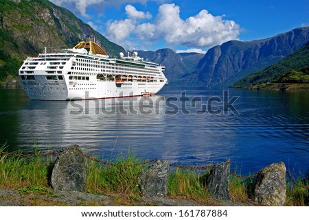 Mountainous landscape in Norway with a cruise liner in the fjord.