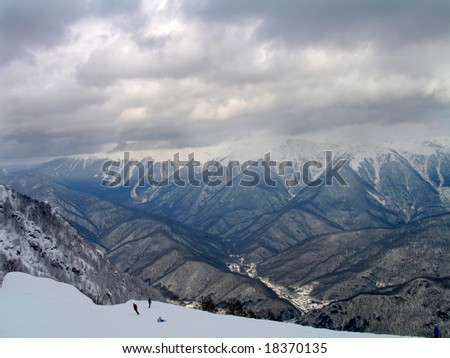 Mountainous snow slope with row of peaks in the background. - stock photo