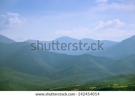 Mountainous terrain and cloudy sky. Mountain hills - natural landscape with green meadow. Beautiful panoramic view of highland. - stock photo