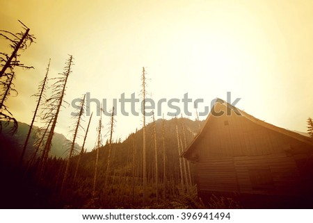 Mountains abstract nature landscape. Wooden house in mountains. - stock photo