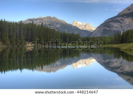 Mountains and boreal forest reflect on the surface of Johnson Lake - Banff National Park, Alberta, Canada