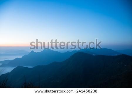 Mountains and fog before sunrise - stock photo