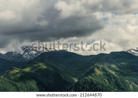 Mountains and hills lit by the sun - stock photo