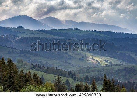 Mountains and storm clouds in the morning. A ray of sunlight shining through the clouds on a small portion of the mountain slope - stock photo