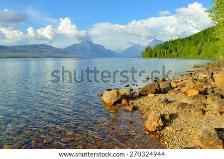 Mountains and the bank of McDonald lake in Glacier National Park, Montana in summer - stock photo