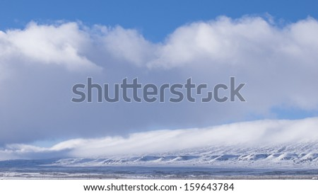 Mountains covered with snow in fog.