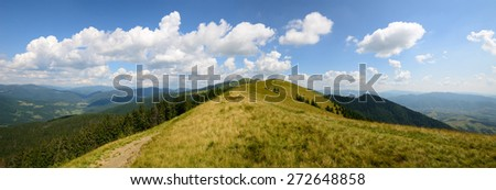 Mountains day panoramic landscape with yellow grasses and a path along the ridge - stock photo