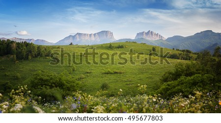 Mountains (Eastern and Western Acheshbok) under a blue sky with clouds. Caucasus, Russia