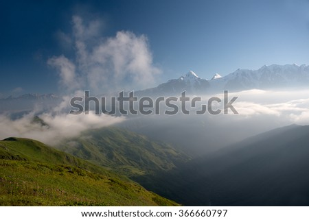 Mountains enshrouded in everpresent mist and clouds. Blue sky is in background. Caucasus Mountain - Georgia.