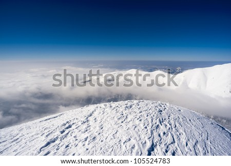 Mountains in a sunny day with clouds in valley