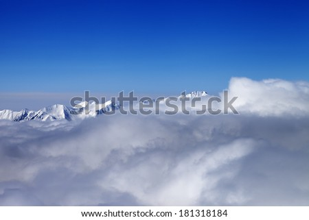 Mountains in clouds at nice sun day. Caucasus Mountains, Georgia, Gudauri. View from ski slope. - stock photo