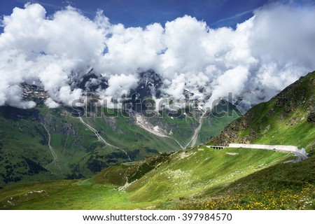 Mountains in clouds. Green mountains. Mountain landscape. Mountain meadow view. Grossglockner Mountain Road, Austria. Mountain landscape and mountain road. Mountains peaks in clouds. Misty mountains. - stock photo
