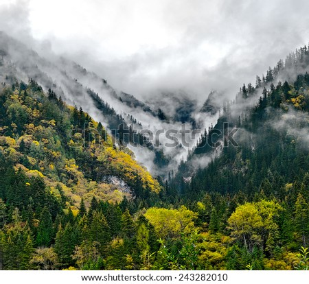 Mountains in the clouds. Jiuzhaigou Valley was recognize by UNESCO as a World Heritage Site and a World Biosphere Reserve - China - stock photo