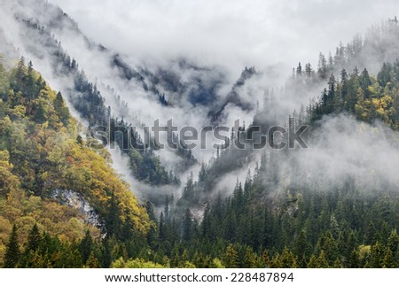 Mountains in the mist. Jiuzhaigou Valley was recognize by UNESCO as a World Heritage Site and a World Biosphere Reserve - China - stock photo
