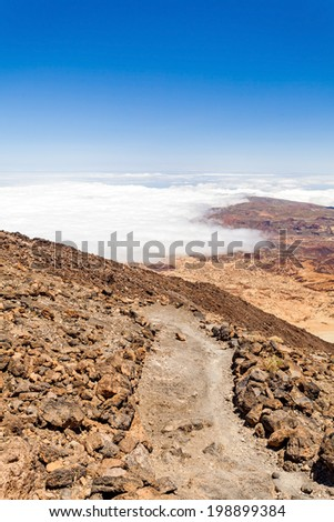 Mountains landscape, hiking trail on volcanic rocks on Teide, blue sky and clouds, Canary Islands, Tenerife in Spain