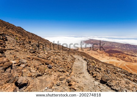 Mountains landscape, hiking trail on volcanic rocks on Teide, blue sky and clouds, Canary Islands, Tenerife in Spain - stock photo