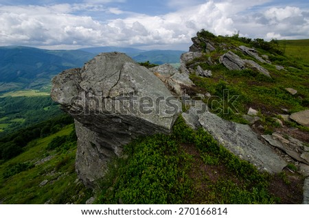 Mountains landscape with grassy hills and slopes and large rock and cloudy sky - stock photo