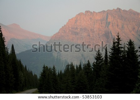 Mountains red from sunset with silhouette of tall pines in foreground. - stock photo
