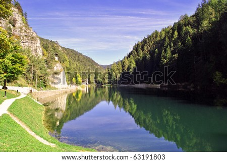 mountains reflected in lake surrounded by pine forests