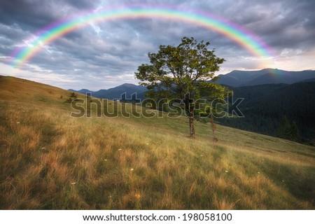 Mountains rural landscape and rainbow - stock photo
