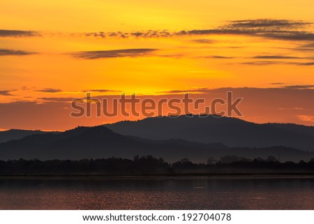 Mountains, sunrise, water in the morning. - stock photo