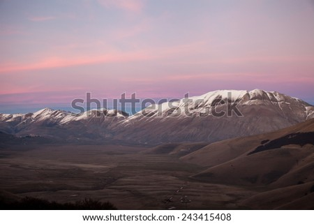 Mountains  with snowy peaks with dusk sky background - stock photo