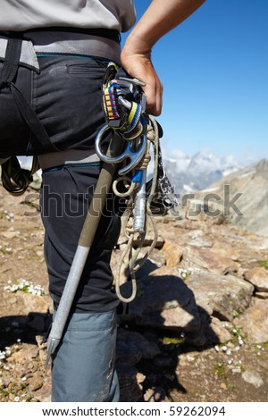 Mountaneer with climbing equipment in the mountains