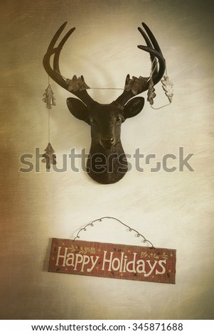 Mounted deer head with garland and holiday sign - stock photo