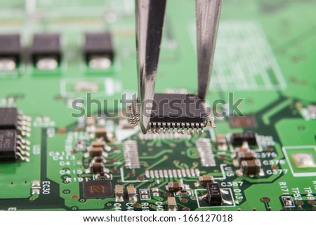 Mounting microchip on green electronic circuit board with tweezers - stock photo
