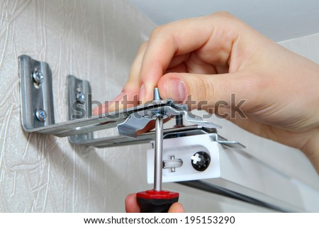 mounting vertical blinds, Vertical Blinds Outside Mount Valance Clip, hand with a screw close up, vertical blinds mounting brackets - stock photo
