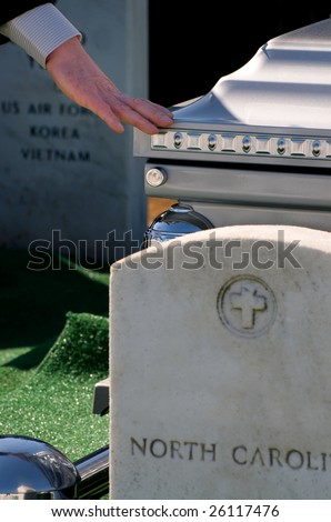 Mourner touching casket at Arlington National Cemetery - stock photo