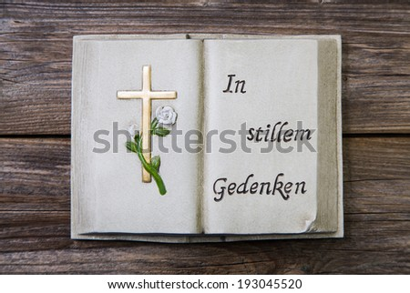 "Mourning: Book of white stone with a golden gross and german text ""thinking of you in silence"" - stock photo"