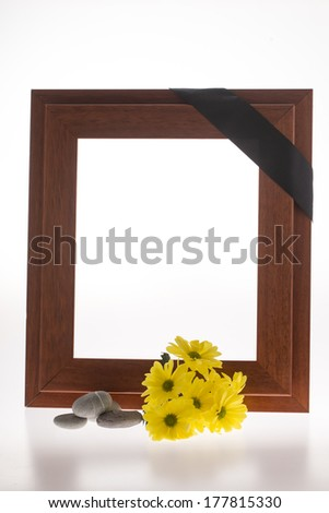 mourning frame with yellow flower and stones on white - stock photo