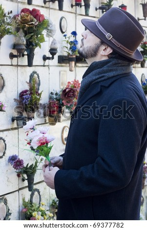 Mourning Man Standing on a Grave at the Cemetery - stock photo