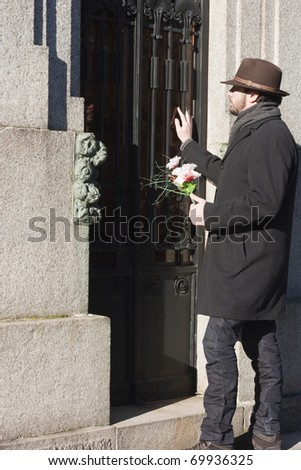 Mourning Man Visiting the Family Vault in a Graveyard - stock photo