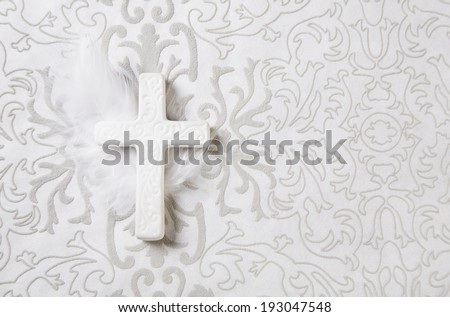 Mourning: white ceramic cross with feather for a obituary notice. - stock photo