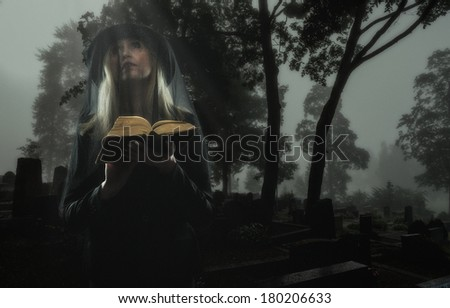Mourning widow praying on a grave at the cemetery