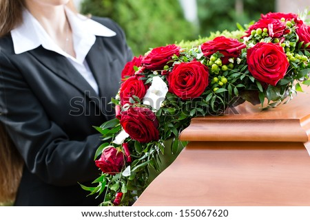 Mourning woman on funeral with red rose standing at casket or coffin - stock photo