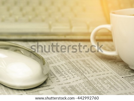mouse , a cup of coffee and keyboard on a newspaper with a very shallow depth of field with copy space for text  with burst light - stock photo