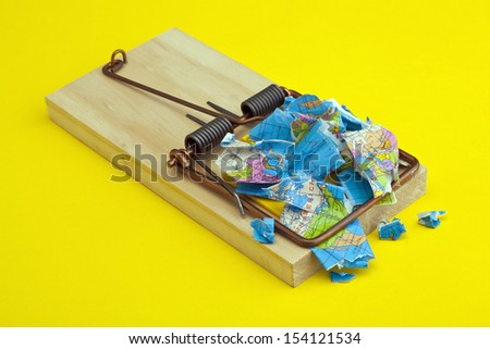 Mouse trap with a trapped and broken world concept on yellow background - stock photo