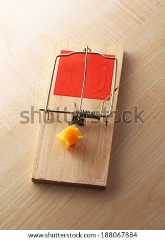Mousetrap with cheese on wooden background