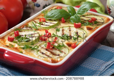 Moussaka dish with zucchini, eggplant and chili pepper, traditional greek food - stock photo
