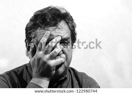 moustached unshaven middle-aged man close the face by hand - stock photo