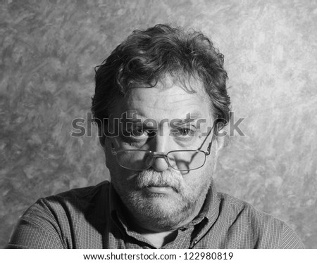 moustached unshaven middle-aged man with glasses