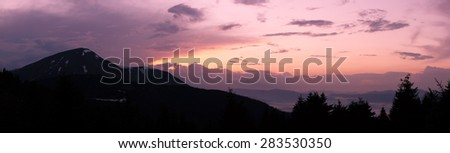 Moutain at sunset wih path and sun - stock photo