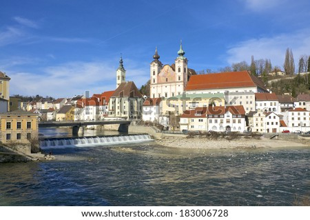 Mouth of the Steyr in the Enns River in the town Steyr in Upper Austria. In the foreground the St.Michaels Church with gable Fresco. Steyr is the 3rd largest town in Upper Austria - stock photo